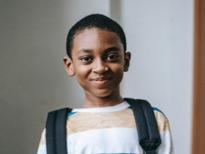 Young child with backpack smiling at the camera